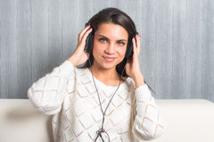 Música que escucha de la mujer joven con los auriculares en sitio en casa en la mirada del sofá en la cámara Imágenes de archivo libres de regalías