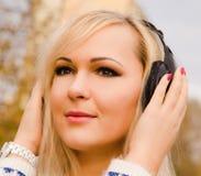 Música que escucha de la mujer joven en auriculares en la ciudad Fotografía de archivo libre de regalías