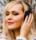 Música que escucha de la mujer joven en auriculares en la ciudad Imagen de archivo