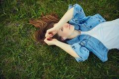 Música que escucha de la mujer joven en el parque Imagenes de archivo
