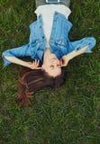 Música que escucha de la mujer joven en el parque Imágenes de archivo libres de regalías