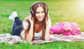 Música que escucha de la mujer joven en el parque del verano fotos de archivo libres de regalías