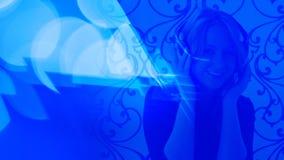 Música que escucha de la mujer joven, fondos ligeros azules almacen de metraje de vídeo