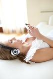 Música que escucha de la mujer joven que miente en una cama Imagenes de archivo