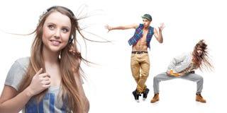 Música que escucha de la mujer joven y dos bailarines en fondo Imagen de archivo