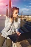 Música que escucha de la mujer joven y el mecanografiar en el ordenador portátil al aire libre Fotos de archivo libres de regalías