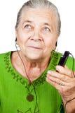 Música que escucha de la mujer mayor en el teléfono móvil fotografía de archivo