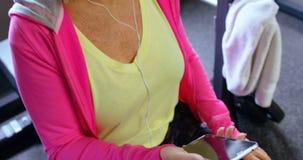 Música que escucha de la mujer mayor en el teléfono móvil en el estudio 4k de la aptitud almacen de metraje de vídeo