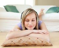 Música que escucha de la mujer Relaxed que miente en el suelo Fotos de archivo libres de regalías