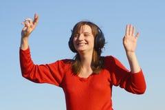 Música que escucha de la mujer sonriente imagenes de archivo
