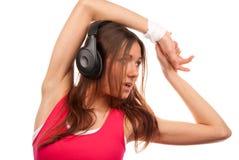 Música que escucha de la mujer triguena bonita de la aptitud Foto de archivo