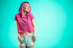 Música que escucha de la señora cabelluda rosada en auriculares en fondo azul Foto de archivo libre de regalías