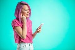Música que escucha de la señora cabelluda rosada en auriculares en fondo azul Imagenes de archivo