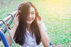Música que escucha de la señora del teléfono elegante con los auriculares al aire libre Fotografía de archivo libre de regalías