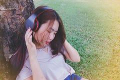 Música que escucha de la señora del teléfono elegante con los auriculares al aire libre Imagenes de archivo