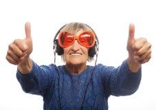 Música que escucha de la señora mayor divertida y el mostrar pulgares para arriba Foto de archivo