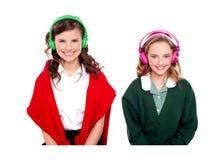 Música que escucha de las colegialas a través de los auriculares Fotos de archivo