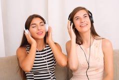 Música que escucha de los amigos en los auriculares que se sientan en el sofá en sitio Imagen de archivo