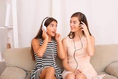 Música que escucha de los amigos en los auriculares que se sientan en el sofá en sitio Fotos de archivo