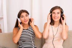Música que escucha de los amigos en los auriculares que se sientan en el sofá en sitio Imagen de archivo libre de regalías