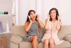 Música que escucha de los amigos en los auriculares que se sientan en el sofá en sitio Foto de archivo