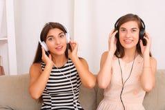 Música que escucha de los amigos en los auriculares que se sientan en el sofá en sitio Fotografía de archivo