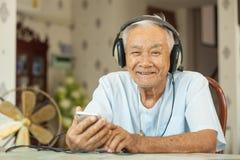 Música que escucha de los auriculares asiáticos felices del hombre mayor imagenes de archivo
