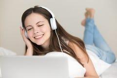 Música que escucha de los auriculares de la mujer que lleva joven en el ordenador portátil en casa Imagenes de archivo