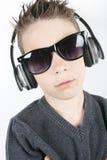 Música que escucha de los auriculares del muchacho que lleva joven adentro Fotos de archivo
