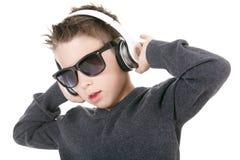 Música que escucha de los auriculares del muchacho que lleva joven adentro Fotografía de archivo