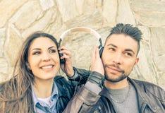 Música que escucha de los pares con el auricular Imagen de archivo libre de regalías