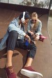 Música que escucha de los pares del inconformista con los auriculares y el siiting en parque del monopatín Fotografía de archivo