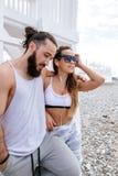 Música que escucha de los pares jovenes con los auriculares mientras que se relaja en Pebble Beach foto de archivo libre de regalías