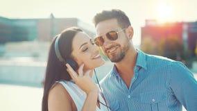 Música que escucha de los pares jovenes felices por los auriculares al aire libre foto de archivo