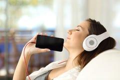 Música que escucha de reclinación de la muchacha y mostrar la pantalla del teléfono Foto de archivo