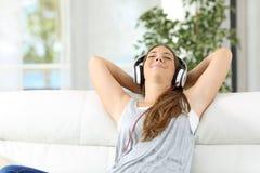 Música que escucha de relajación de la mujer en casa Fotos de archivo