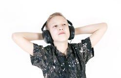 Música que escucha del adolescente con los auriculares, aislados en blanco puro Fotos de archivo