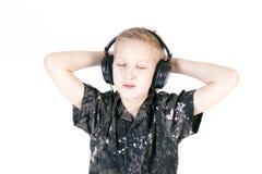 Música que escucha del adolescente con los auriculares, aislados en blanco puro Fotografía de archivo libre de regalías