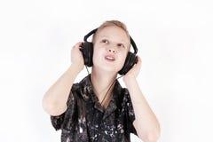 Música que escucha del adolescente con los auriculares, aislados en blanco puro Imagen de archivo libre de regalías