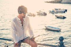 Música que escucha del adolescente con los auriculares de la tableta en un vacat Foto de archivo