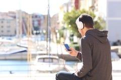 Música que escucha del adolescente del teléfono elegante Imagenes de archivo
