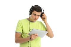 Música que escucha del adolescente en el fondo blanco Imagen de archivo libre de regalías
