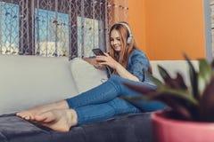 Música que escucha del adolescente feliz en línea del teléfono elegante fotografía de archivo libre de regalías