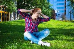 Música que escucha del adolescente feliz en parque Imagenes de archivo