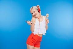 Música que escucha del adolescente femenino en smartphone Fotos de archivo libres de regalías