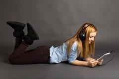 Música que escucha del adolescente lindo feliz en sus auriculares Foto de archivo