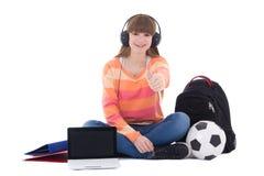 Música que escucha del adolescente que se sienta en auriculares con el ordenador portátil Imagenes de archivo