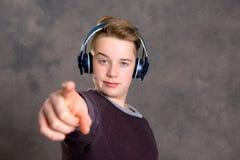 Música que escucha del adolescente y el señalar adentro a la cámara Foto de archivo