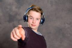 Música que escucha del adolescente y el señalar adentro a la cámara Imagen de archivo