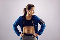 Música que escucha del atleta de sexo femenino con el teléfono celular Fotos de archivo